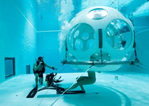 "Belgians Florence Lutje Spelberg and Nicolas Mouchart dive into ""The Pearl"", a spheric dining room placed 5 metres underwater in the NEMO33 diving center, one of the world's deepest pools (33 metre/36 yards) built to train professional divers, before enjoying a meal inside, in Brussels, Belgium January 30, 2017. Picture taken January 30, 2017 REUTERS/Yves Herman"